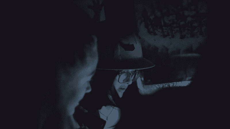 Two young women with flash light and construction hat looking for clues in the dark