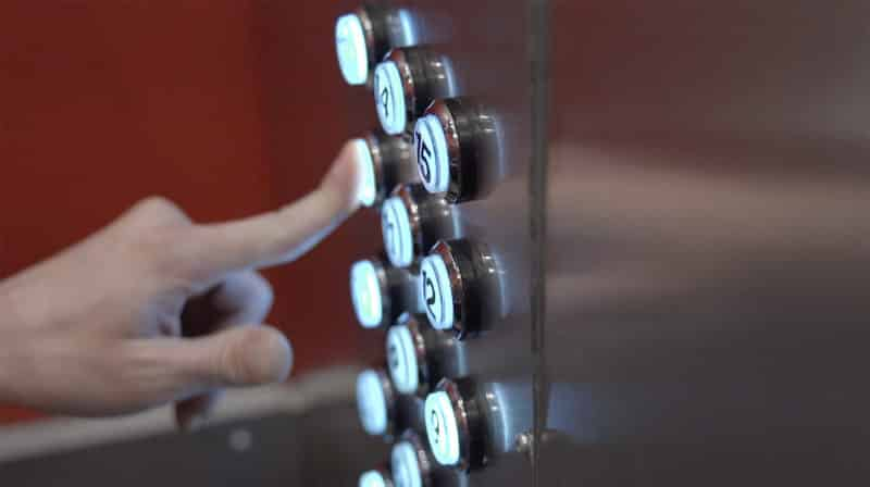 finger pushing an elevator button close up